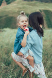 The young mother and daughter on green grass Stock Photos
