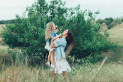 The young mother and daughter on green grass Stock Photo
