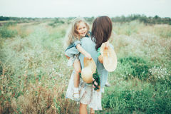The young mother and daughter on green grass Stock Images