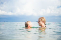 Young mother and daughter have fun swim on island in tropical oc Royalty Free Stock Images