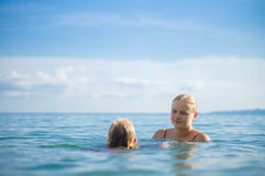 Young mother and daughter have fun swim on island in tropical oc Stock Images
