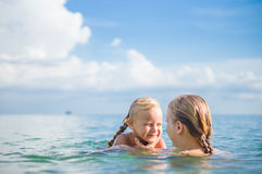 Young mother and daughter have fun swim on island in tropical oc Royalty Free Stock Photography
