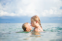 Young mother and daughter have fun swim on island in tropical oc Royalty Free Stock Photo