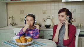 Young mother and cute daughter having breakfast in the morning in kitchen at home. Little girl listening music with stock video