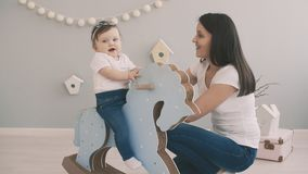 Young mother and daughter having fun with toy horse in slow motion indoor. Baby riding blue horse. Family concept in white t-shirts and jeans stock video footage