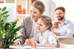 Young mother and daughter hugging and looking on monitor in business office Royalty Free Stock Photos