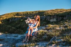 Young mother and daughter, hugging and playing in a golden field of sunshine. Young mother and daughter, hugging and playing in a golden field of sunshine while stock photos