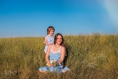 Young mother and daughter, hugging and playing in a golden field of sunshine. Young mother and daughter, hugging and playing in a golden field of sunshine while stock photography