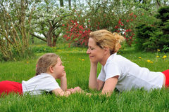 Young mother and daughter laying on the grass Stock Photo