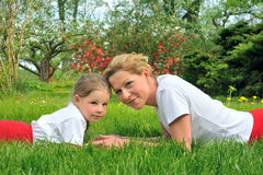 Young mother and daughter laying on the grass Royalty Free Stock Photo