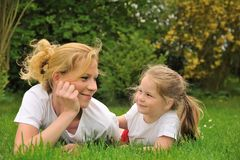 Young mother and daughter laying on the grass Royalty Free Stock Images