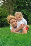 Young mother and daughter laying on the grass Royalty Free Stock Photography