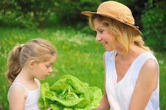 Young mother and daughter with lettuce Stock Image