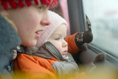 Young mother with daughter look to bus window Stock Photos