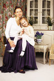 Young mother with daughter at luxury home interior vintage Royalty Free Stock Photos