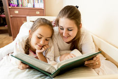 Young mother and daughter lying in bed and viewing photo album Stock Photos