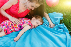 Young mother with daughter lying on blue blanket at lawn Royalty Free Stock Photo