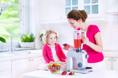 Young mother and daughter making fresh fruit jiuce Stock Photos