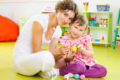 Young mother and daughter painting Easter eggs Royalty Free Stock Images