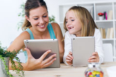 Young mother and daughter playing with digital tablet at home. Stock Image