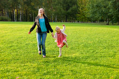 Young mother and daughter playing in the park Stock Photos