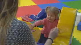 Young mother and daughter are playing in the playroom, climbing on an inflatable hill stock footage