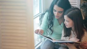 Mother and daughter reading book stock footage