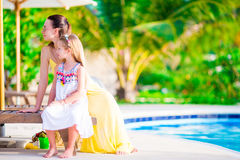 Young mother and daughter relaxing near swimming pool Stock Photo