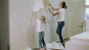 A young mother and a daughter removing wallpaper. A young pregnant mother and a small blond daughter removing wallpaper. They both wear jeans and white t stock video footage