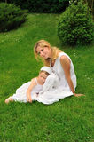Young mother and daughter resting in meadow Royalty Free Stock Photography