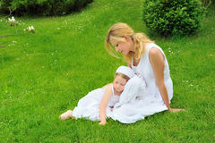 Young mother and daughter resting in meadow Stock Photo