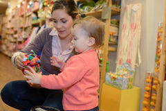 Young mother daughter shopping at toy store Stock Photo