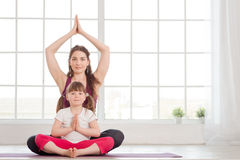 Young mother and daughter sitting in lotus position Stock Photography