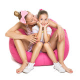 Young mother and daughter sitting on pink bean bag. Closeup of pretty young mother and daughter sitting on pink bean bag. Mother kissing her daughter on cheek Royalty Free Stock Images