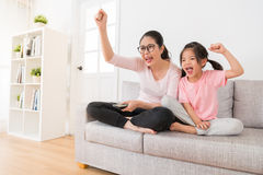 Young mother and daughter sitting on the sofa. In the living room watching sports game through the home TV to celebrate the soccer team victory showing happy stock photography