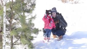 Young mother and daughter in the snowy forest. Mom and daughter talk and rejoice stock footage