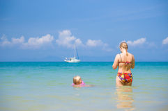 Young mother and daughter swim in clear tranquil ocean with yach Stock Image