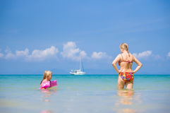 Young mother and daughter swim in clear tranquil ocean with yach Stock Photos