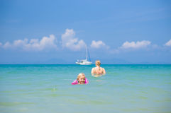 Young mother and daughter swim in clear tranquil ocean with yach Stock Photo