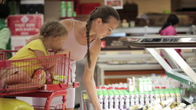 Young mother with daughter in trolley selecting slicing fruits at supermarket. Young attractive mother with little daughter in trolley selecting slicing fruits stock video footage