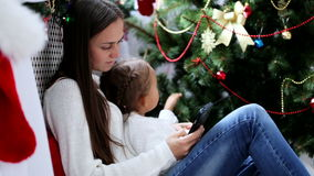 Young mother and daughter using smartphone in a Christmas decorated interior. Young mother and daughter sitting on the floor and using smartphone in a Christmas stock video