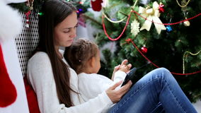 Young mother and daughter using smartphone in a Christmas decorated interior. Young mother and daughter sitting on the floor and using smartphone in a Christmas stock video footage