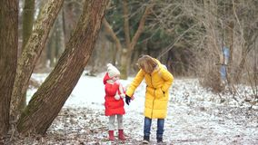 Young mother and daughter on a walk in winter park. They are dressed in bright down jackets stock video