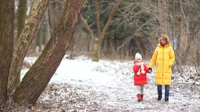 Young mother and daughter on a walk in winter park. They are dressed in bright down jackets stock video footage