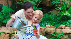Young mother and daughter watering plants Royalty Free Stock Photos