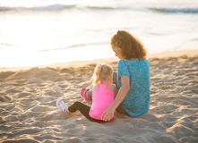 Young mother and daughter in workout gear sitting on beach Stock Photos