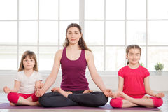 Young mother and daughters doing yoga exercise Royalty Free Stock Photography