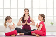 Young mother and daughters doing yoga exercise Royalty Free Stock Photos