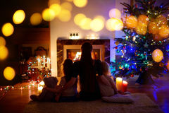 Young mother and daughters sitting by a fireplace on Christmas Stock Photography