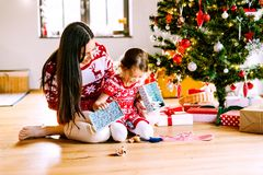 Young mother with daugter at Christmas tree at home. Royalty Free Stock Images